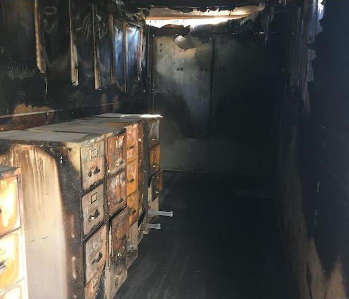 Room with fire and smoke damage around metal filing cabinets