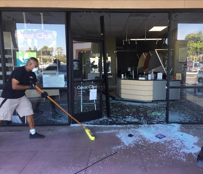 Service employee cleaning up broken glass after vandalism at a local storefront
