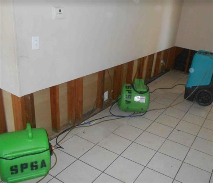 SERVPRO Drying equipment in water damaged room.  Flood cuts on drywall